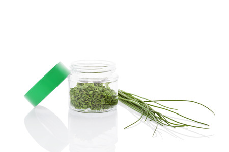 herbs white background: Fresh chives and dry chive spice in glass jar isolated on white background Stock Photo