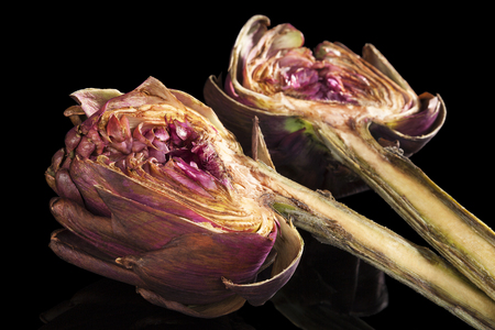 culinary: Fresh artichoke isolated on black background. Culinary healthy vegetable eating. Stock Photo