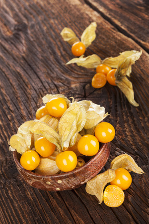 husk tomato: Physalis, groundcherries in bowl on brown textured aged background