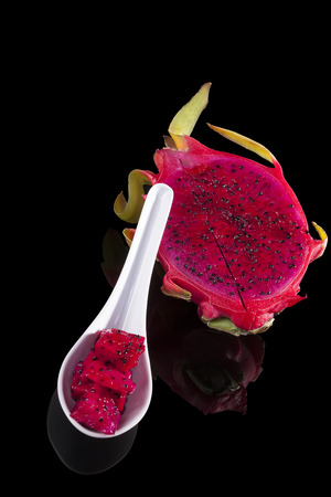 dragon vertical: Dragon fruit pieces on spoon isolated on black background