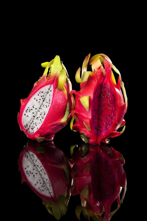 dragon vertical: Red and white dragon fruits isolated on black background