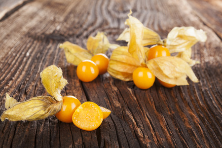husk tomato: Physalis, groundcherriesl on brown textured aged background Stock Photo