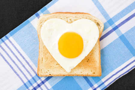 sunnyside: Sunny side up egg in heart shape on toast, top view Stock Photo