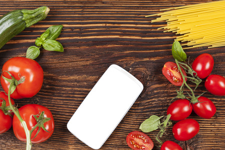 information age: Fresh vegetables and pasta on wooden table with smartphone and empty white screen. Stock Photo
