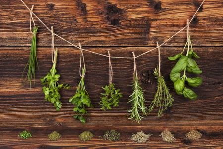 Aromatische kruiden, basilicum, koriander, peterselie, bieslook, munt en rozemarijn opknoping op string op oude landelijke stijl houten achtergrond.