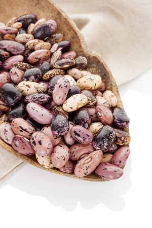 pinto beans: Pinto beans on wooden scoop on beige table cloth.   Stock Photo