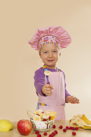 eating habits: Little girl in purple cook hat and tablier making fruit salad. Healthy eating habits.