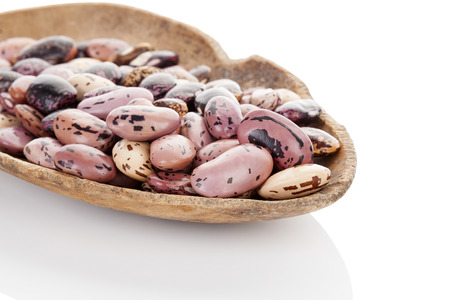 pinto beans: Dry pinto beans on old wooden scoop isolated on white background.