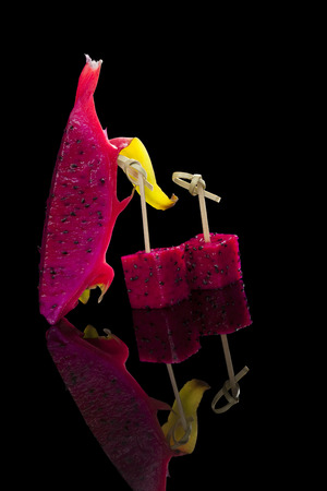 culinary arts: Pink dragon fruit isolated on black background.