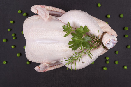 Raw whole chicken with fresh herbs and peas on black stone background, top view.  Archivio Fotografico