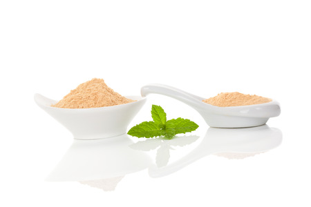 adaptogen: Maca root powder in bowl and spoon isolated on white background.
