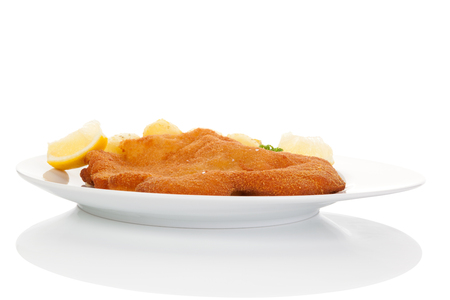 european cuisine: Delicious wiener schnitzel on plate isolated on white background with reflection. Traditional european cuisine.