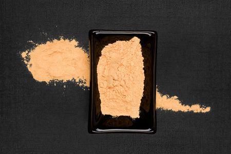 maca: Maca powder on black background, top view