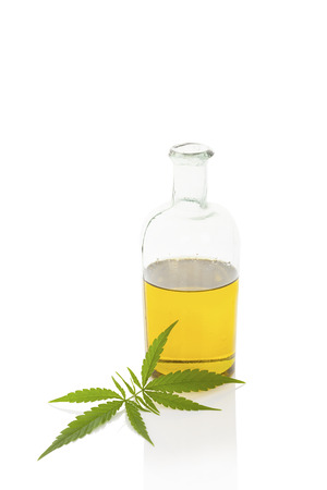 Hemp oil and cannabis leaf isolated on white background