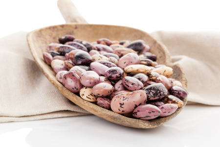pinto beans: Pinto beans on wooden scoop on beige table cloth