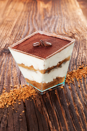 instant coffee: Tiramisu dessert with coffee beans and instant coffee on wooden textured table Stock Photo