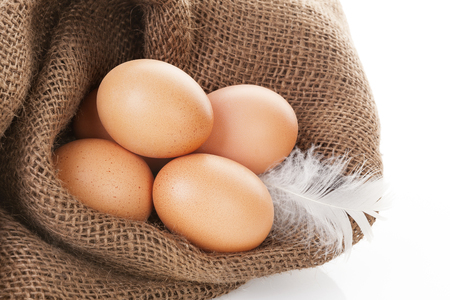 burlap bag: Organic chicken eggs in burlap bag isolated on white background. Stock Photo