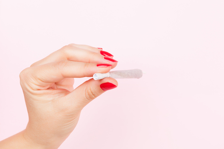 reefer: Female hand with red fingernails holding cannabis joint isolated on pink background