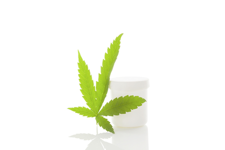 ganja: Cannabis leaf and white container isolated on white background with reflection
