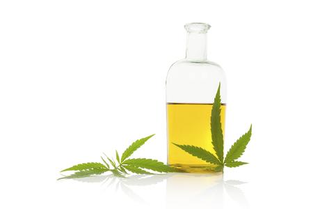 marihuana: El aceite de c��amo y la hoja de cannabis aislado en el fondo blanco. Aceite de cannabis saludable.