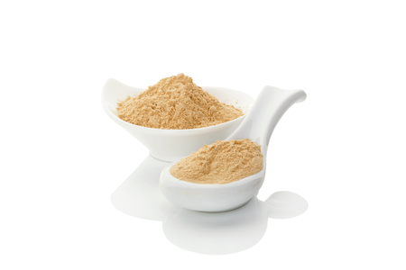 Maca powder on spoon and in a bowl isolated on white background Standard-Bild