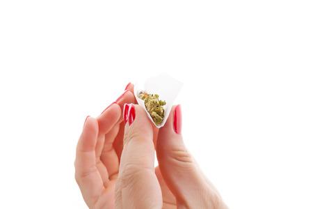 marihuana: Manos aisladas sobre fondo blanco rueda una junta de cannabis Foto de archivo