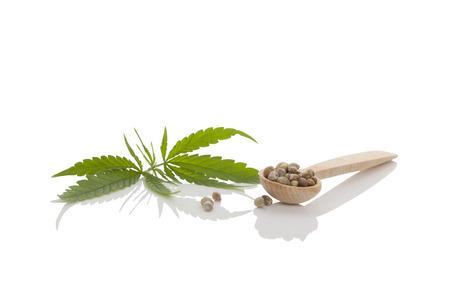 semilla: Semillas de cannabis en la cuchara de madera y hoja de cannabis aislado en el fondo blanco.