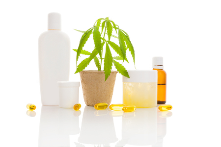 ganja: Moisturizer, cream, shampoo, oil and young cannabis plant in plant pot isolated on white background Stock Photo