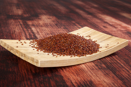red quinoa: Red quinoa seeds on wooden plate on wooden background.