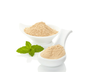 adaptogen: Maca powder on spoon and in a bowl and mint leaf isolated on white background Stock Photo