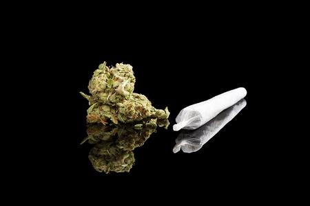 Marijuana background. Cannabis cigarette joint, bud and hemp leaves isolated on black background. Addictive drug or alternative medicine. Stockfoto