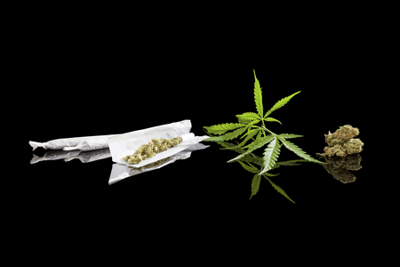 addictive: Marijuana background. Cannabis cigarette joint, bud and hemp leaves isolated on black background. Addictive drug or alternative medicine. Stock Photo
