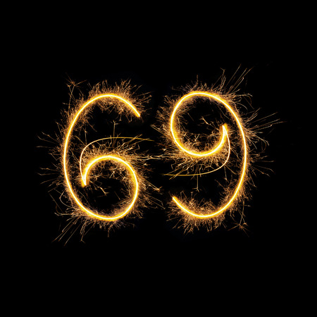 sexual position: Number 69 in sparkling digits isolated on black background. Symbol of sexual position 69.