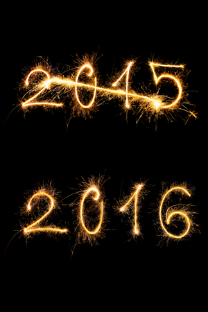 comming: Strikethrough 2015 and 2015 digits made of sparkling light isolated on black background. Old year going, new year comming.