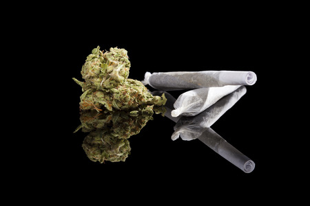 addictive: Marijuana background. Cannabis cigarette joint, bud and hemp leaves isolated on black background. Addictive drug or alternative medicine. Stock Photo