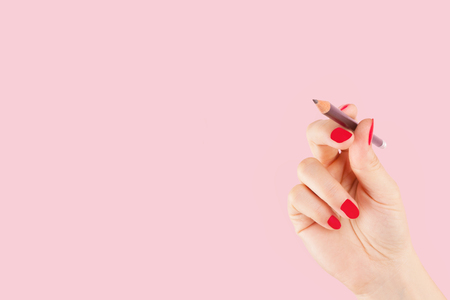 copy writing: Female hand with red fingernails holding a pencil isolated on pink background. Creativity and copy writing, teaching and learning.