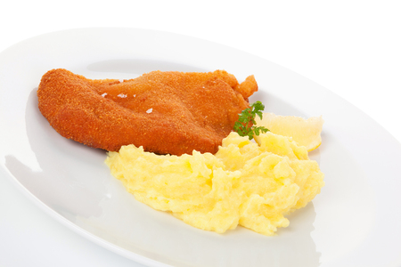 european cuisine: Delicious wiener schnitzel with mashed potatoes on plate on white background. Traditional european cuisine. Stock Photo