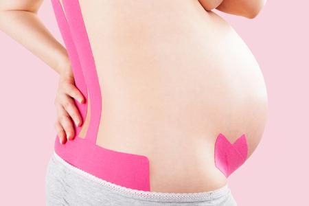 dolor espalda: Hermosa mujer embarazada con cinta de Kinesio en su espalda. El dolor de espalda en el embarazo, la terapia de la cinta Kinesio alternativa. Foto de archivo