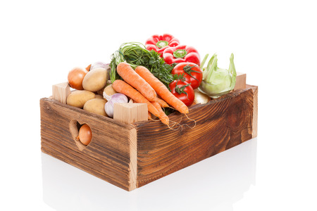 wooden crate: Organic seasonal vegetable in rustic wooden crate isolated on white background. Healthy vegetable eating.