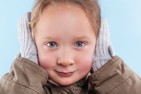 hands covering ears: Little cute girl covering her ears  with hands in gloves against light blue background. Winter season.