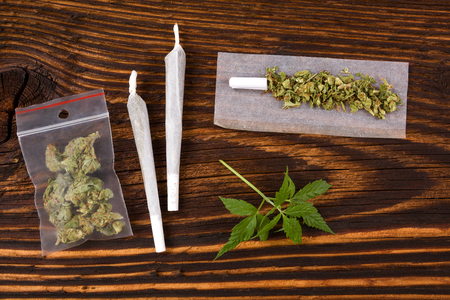 Marijuana background. Cannabis joint, bud in plastic bag and hemp leaves on wooden table. Addictive drug or alternative medicine.