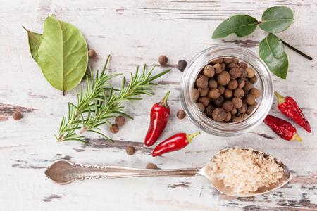 trompo de madera: especias y condimentos tradicionales en el fondo de madera blanca. Hojas de laurel, romero, pimienta de chiles y negro en la mesa de madera, vista desde arriba.