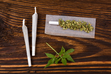 addictive: Marijuana background. Cannabis joint, buds and hemp leaves on wooden table. Addictive drug or alternative medicine. Stock Photo