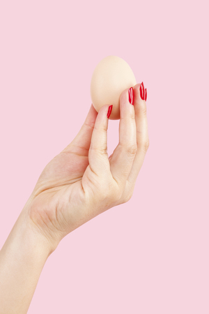 provocation: Female hand with red fingernails holding two eggs isolated on pink background. Feminism, emancipation, provocation and relationship problems.