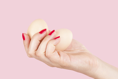 the emancipation: Female hand with red fingernails holding two eggs isolated on pink background. Feminism, emancipation, provocation and relationship problems.