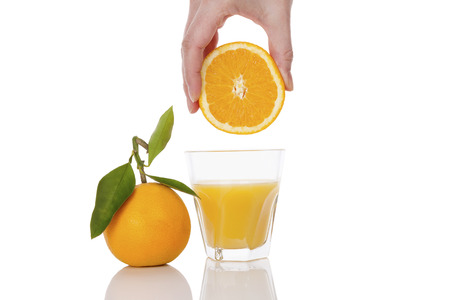 squeeze shape: Freshly squeezed orange juice. Female hand squeezing orange into a glass isolated on white background. Healthy juice drink. Stock Photo