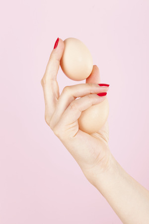 erectile: Erectile dysfunction, impotence. Female hand with red fingernails holding two eggs isolated on pink background.