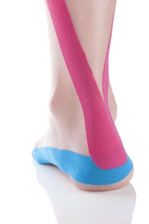 흰색 배경에 고립 된 여성 발 뒤꿈치에 Kinesio 테이프.