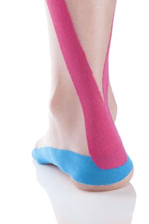 Kinesio tape on female heel isolated on white background.