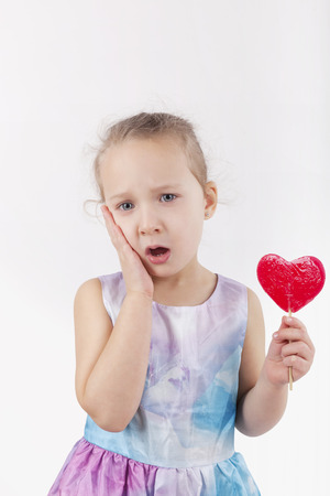 cheek: Little girl with lollypop and hurt teeth holding her cheek.